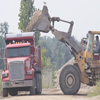 Bulldozer loading dirt and gravel onto back of dump truck on the Gale Briggs Inc property in Charlotte, Michigan